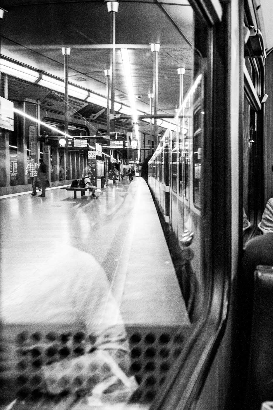 In my last work trip I had to commute on the subway across Munich in Germany. I noticed that each station had an angled mirror at the end of each platform that reflected the platform onto the train window. 7 stops worth of trying timing and settings led to this image - there's always time for photography!